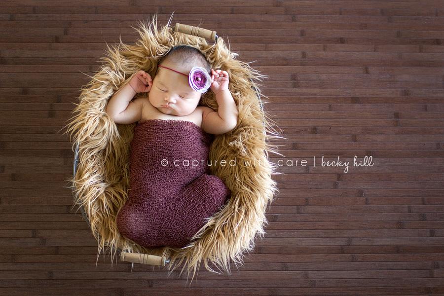 sweet newborn baby girl in basket with fur and purple flower headband