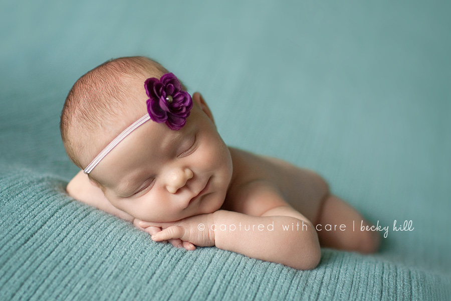 smiling newborn baby girl with purple flower headband on blanket