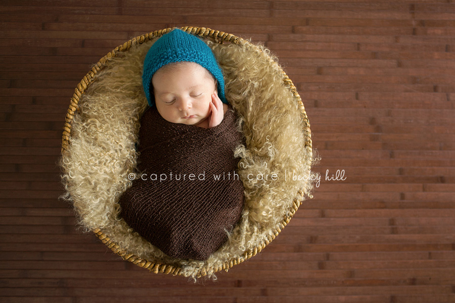 baby in basket in dark brown wrap, hand on cheek, blue knit hat