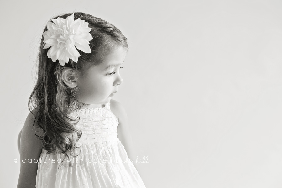 black and white image of 2 year old girl looking down and away from camera, white dress and big white flower in hair