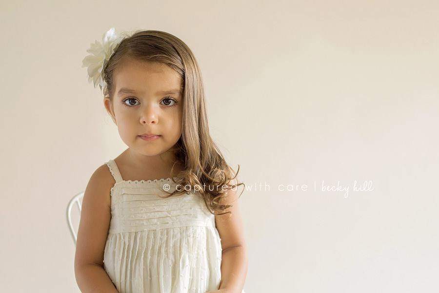 two year old girl portrait, white dress, white flower in hair, eye contact