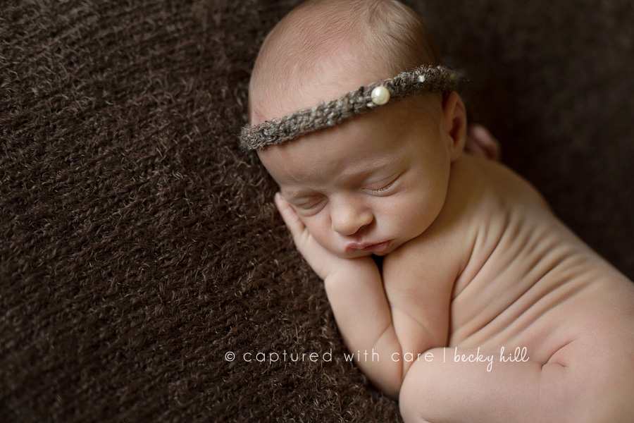 view from above of sweet sleeping newborn infant girl with brown beaded halo, wrinkled newborn skin