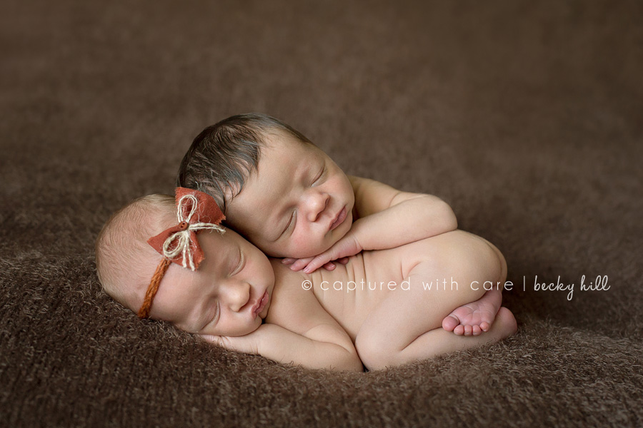 Tiny eight day old fraternal twin babies, boy gently resting on girl's back, amber headband and fabric bow on newborn girl's head, laying on textured brown blanket