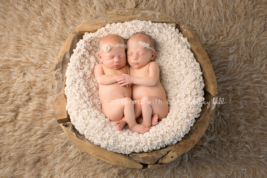 little baby twin girls laying in wooden basket, white headbands, top view