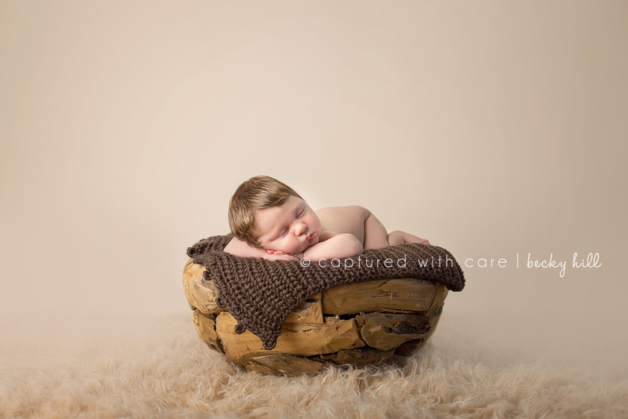 four week old boy sleeping in wooden puzzle bowl on flokati rug, tan background