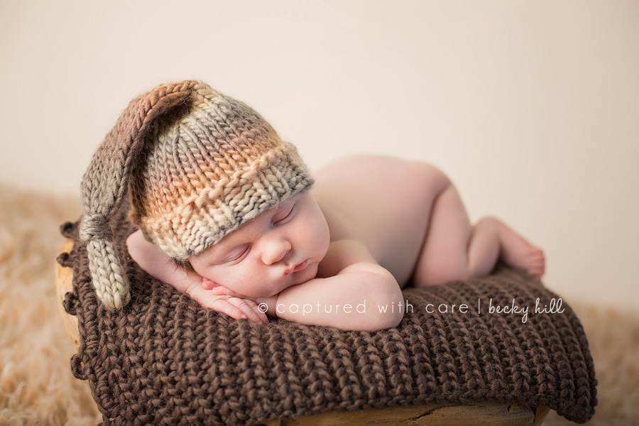 infant resting on brown knit blanket, wearing long gray and orange knit hat, cream background