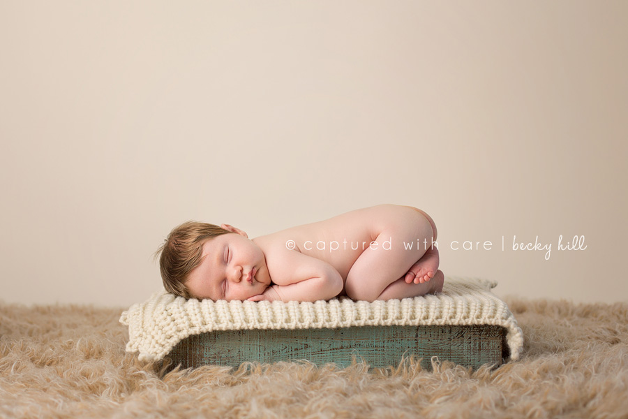 precious one month old boy with lots of hair sleeping on weathered green wood crate, cream background