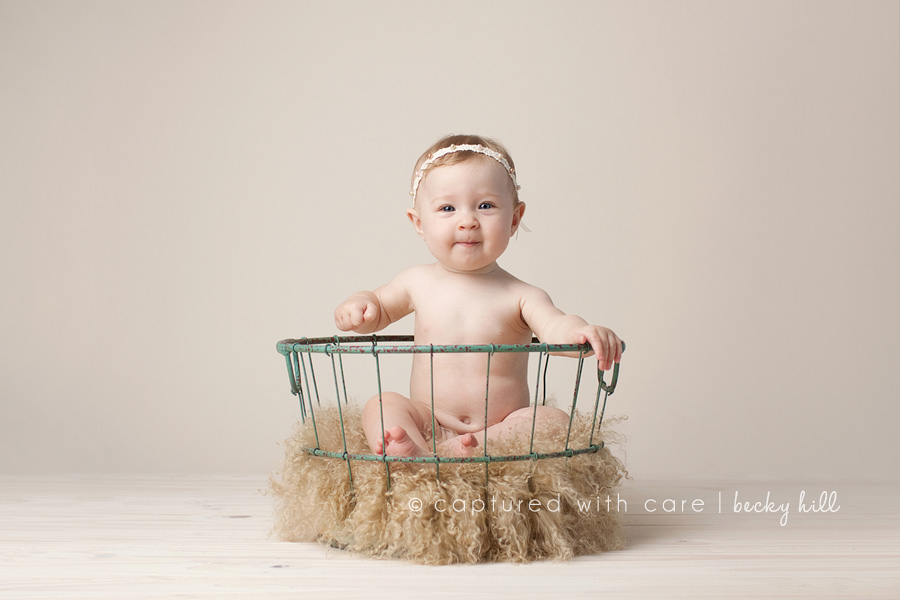 Baby girl smirk with headband in basket with fur