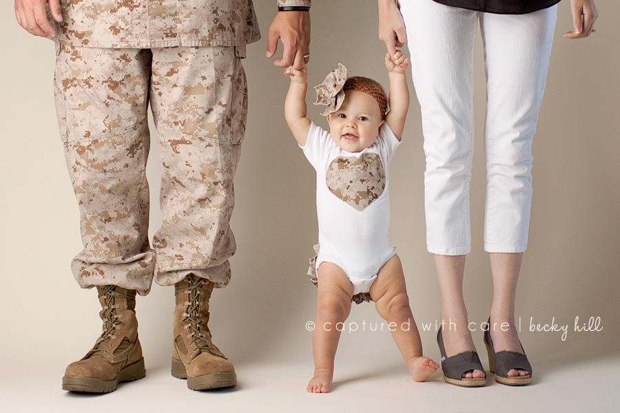 happy baby girl with mom and dad in camouflage armed services uniform, baby camo heart shirt