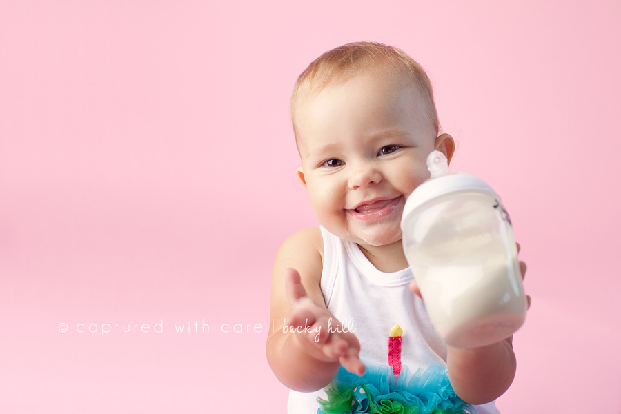 one year old baby girl in birthday shirt holding milk sippy cup