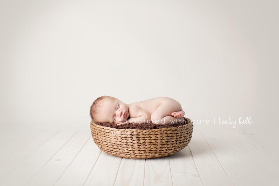 baby sleeping in round basket, white wood floor