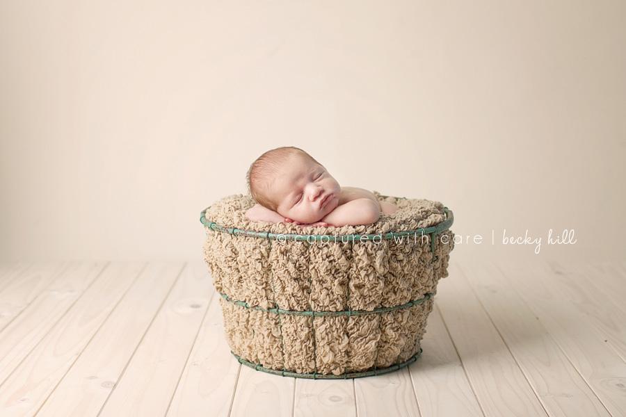 newborn in green basket, light wood floor