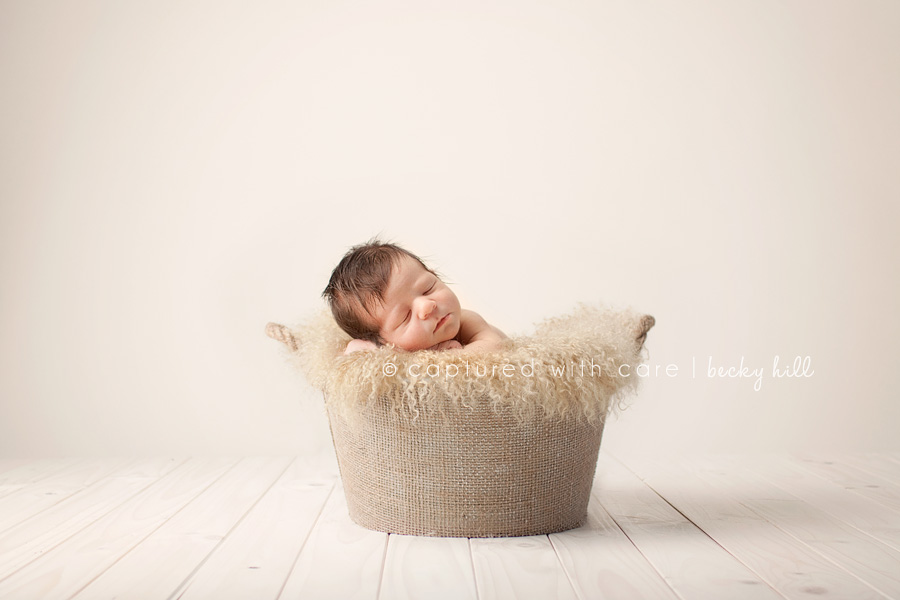 sleepy baby in basket on wood floor