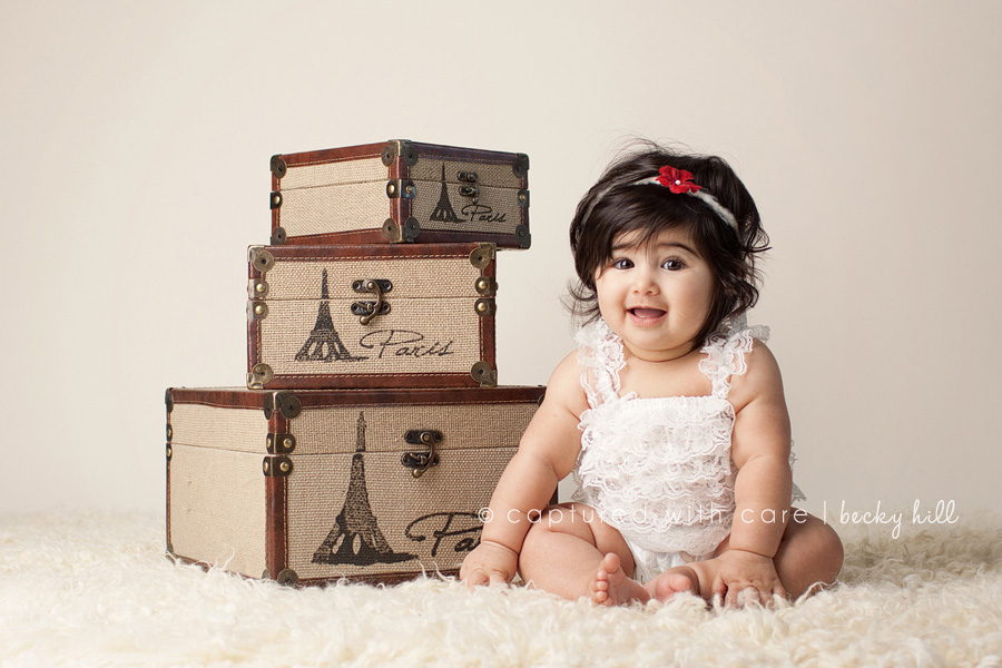 cute baby girl with great head of hair in white dress, luggage packed for Paris