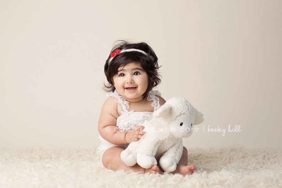 radiant, happy, smiling baby girl in white dress with lamb stuffed animal, beautiful hair