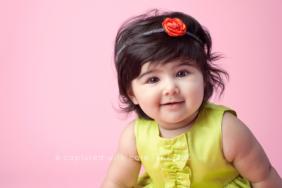 happy 6 month old baby girl, green dress, pink background, orange flower headband
