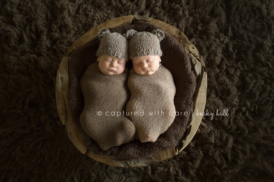 wrapped twin baby boys wearing tan knit bear hats laying in wooden puzzle bowl on chocolate flokati rug