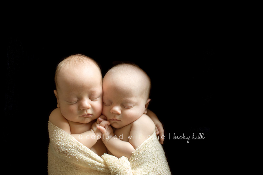 twins wrapped together holding hands and hugging