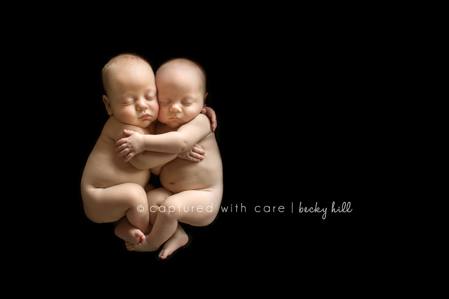 twin baby boy embrace while sleeping, black background
